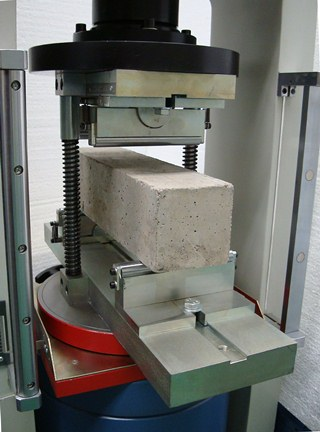 Device for flexural testing on concrete specimens